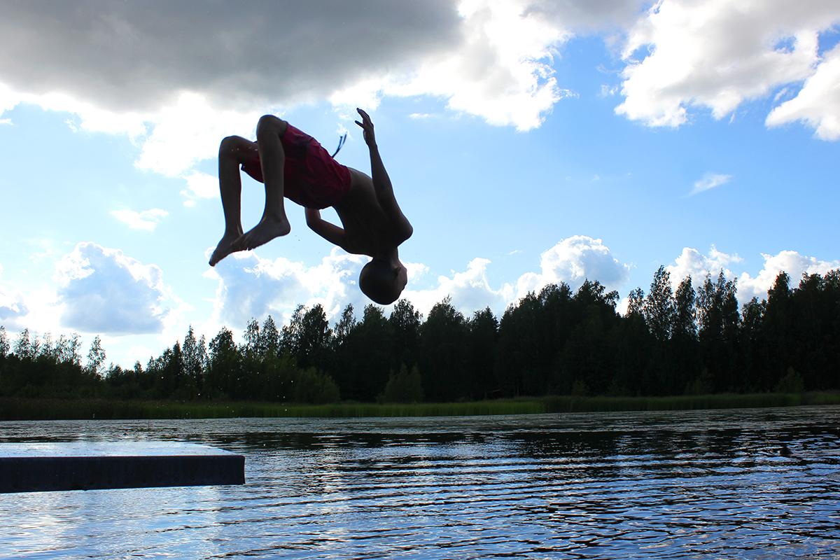 Lapsi hyppää ponkkulaudalta voltin Noitajärveen.