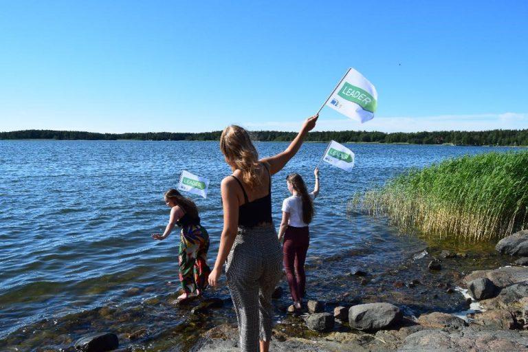 Nuoret leader-lippujen kanssa rannalla