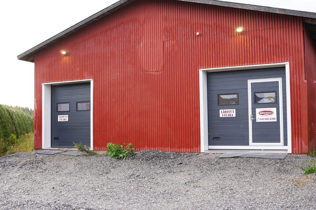 Riistapajan punainen tuotantorakennus ulkoa kuvattuna.