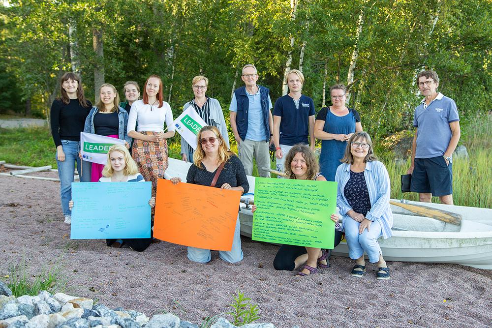 Leader Ravakan hallituksen, nuorisotyöryhmän ja henkilökunnan jäseniä ryhmäkuvassa soutuveneen ympärillä