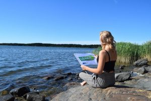 nuori istuu kalliolla merenrannalla