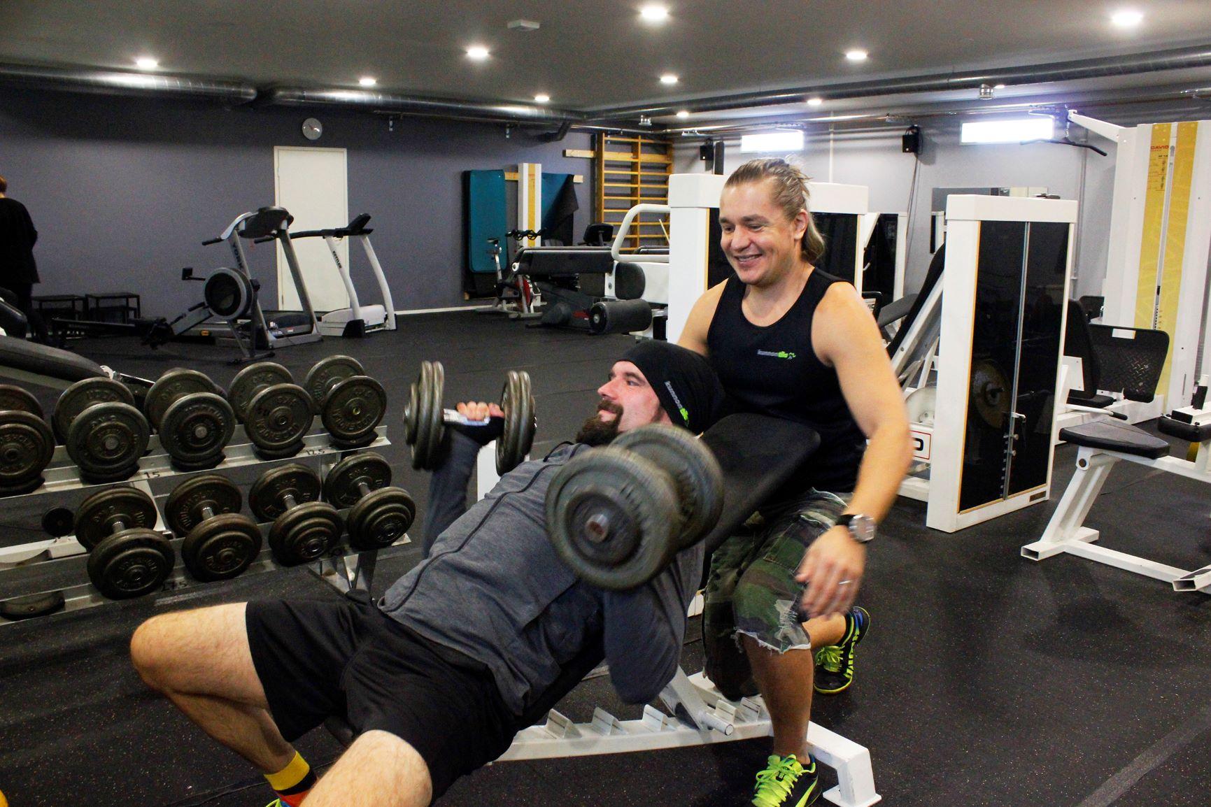 KunnonTila kuntosalilla Hinnerjoella treenaa mies valmentajan avustuksella.