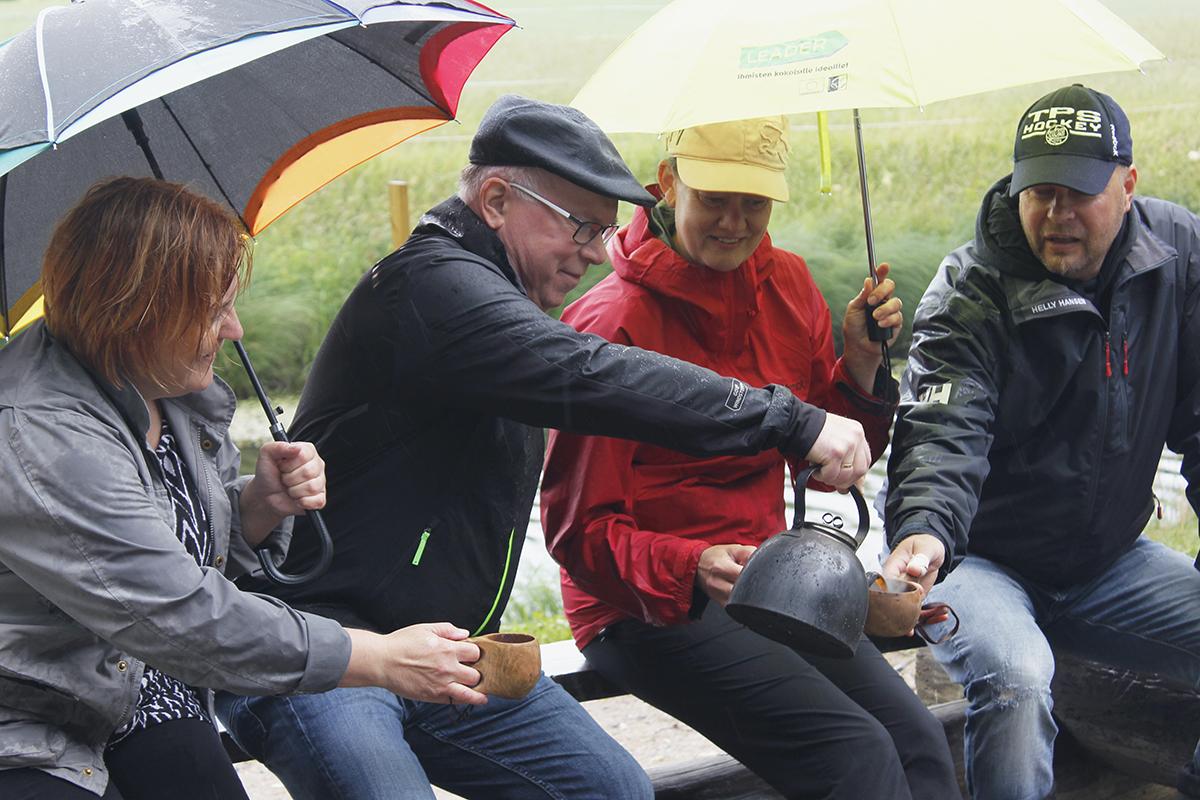 Kari Mäkelä kaataa kahvipannusta kolmelle muulle henkilölle kahvia Asmandian laavulla