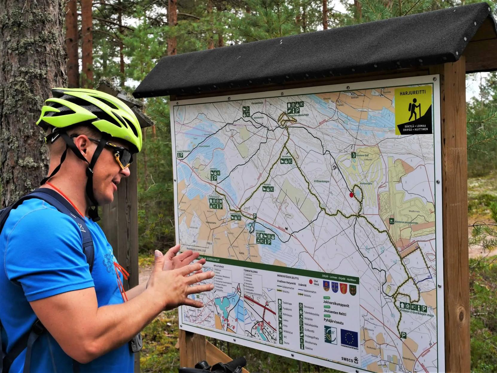 Pyöräilijä katsoo Harjureitin karttaa.