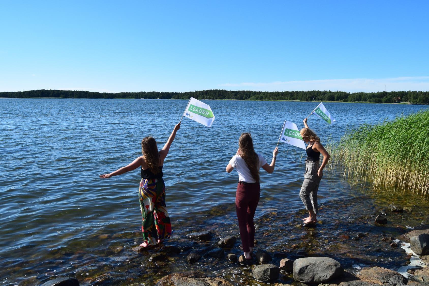 Nuoria rannalla heiluttamassa Leader-lippuja