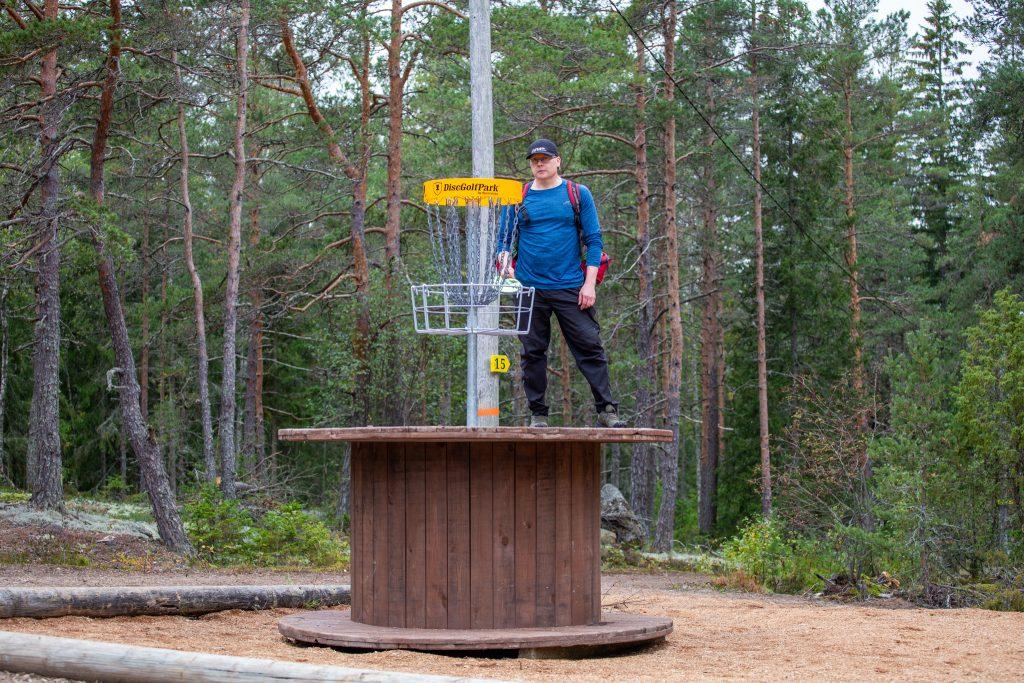 Pekka Siivonen korotetun korin luona Kirikallion frisbeegoldradalla.