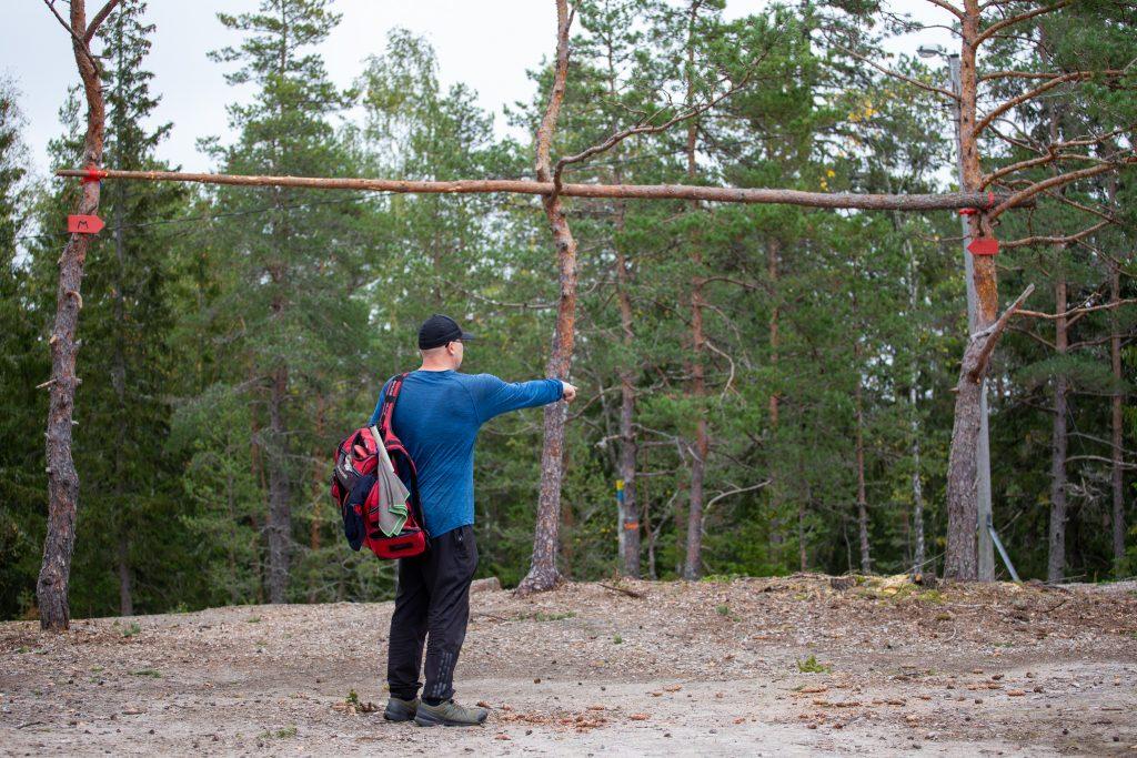 Pekka Siivonen osoittaa missä kiekon lentoradan tulisi olla mandoportin kohdalla Kirikallion frisbeegolfradalla.